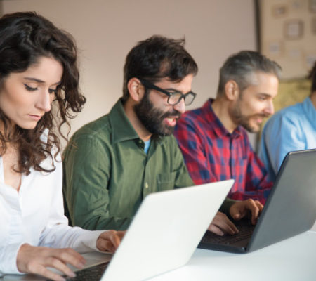 focused-coworkers-using-laptops-meeting-table_74855-3420